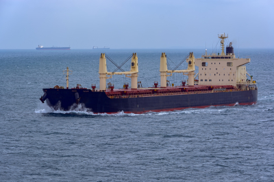 bulk carrier vessel sailing through rough sea